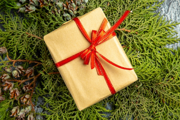 Bottom view small gift tied with red ribbon on pine branches