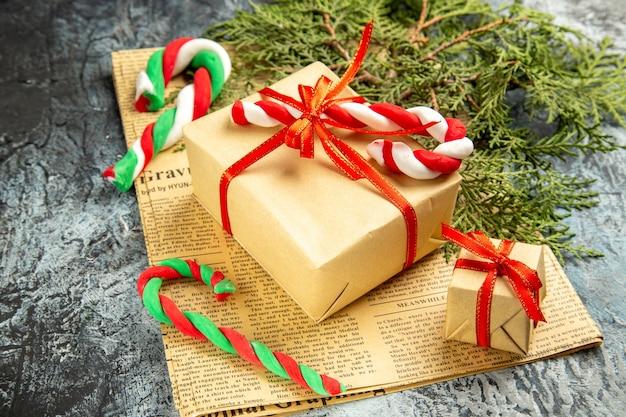 Вид снизу небольшой подарок, перевязанный красной лентой, рождественские конфеты на газете на сером фоне