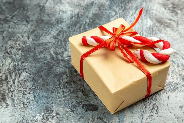 Vista dal basso piccolo regalo legato con nastro rosso caramelle natalizie su grigio