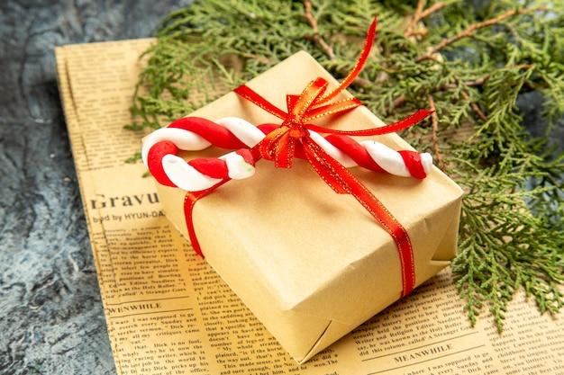 Vista dal basso piccolo regalo legato con nastro rosso caramelle natalizie su giornale su grigio