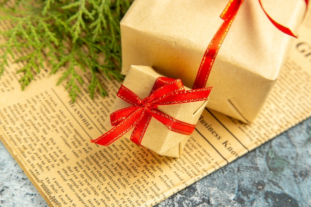 Bottom view small gifts tied with red ribbon on newspaper on dark background
