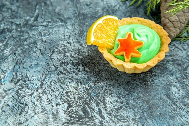 Piccola crostata vista dal basso con pigna di crema pasticcera verde su superficie grigia