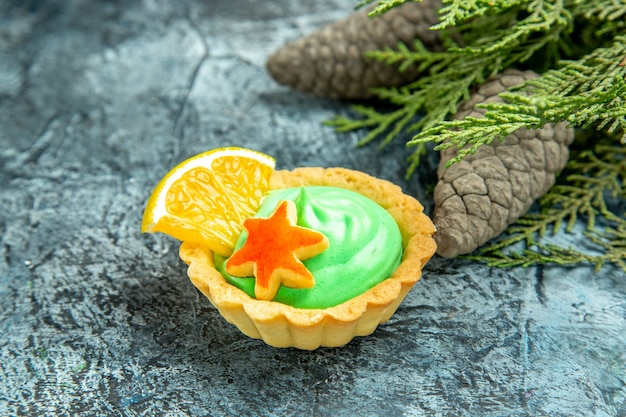 Bottom view small tart with green pastry cream pinecones on grey surface