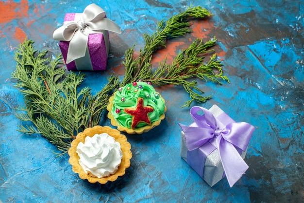 Вид снизу маленькие пирожные маленькие подарки сосновые ветки на синей красной поверхности