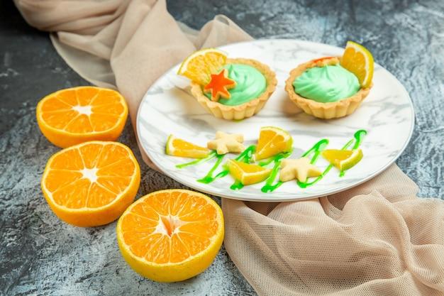 Вид снизу маленькие пирожные с кремом из зеленого теста и долькой лимона на тарелке на бежевой шали, разрезанные апельсины на темной поверхности