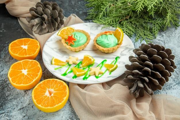 Вид снизу маленькие пирожные с кремом из зеленого теста и долькой лимона на тарелке на бежевой шали, разрезанные апельсины, шишки на темной поверхности