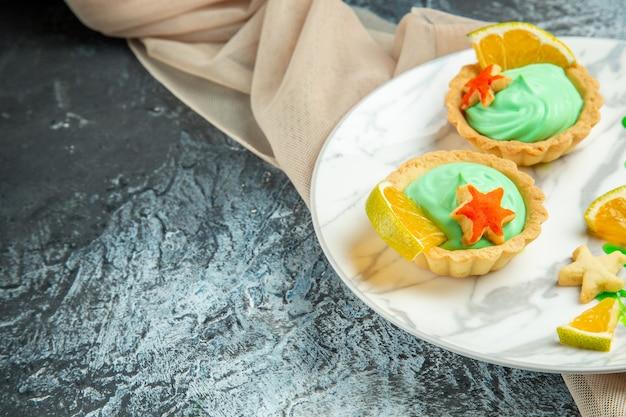 Вид снизу маленькие пирожные с кремом из зеленого теста и ломтиком лимона на тарелке на темной поверхности.
