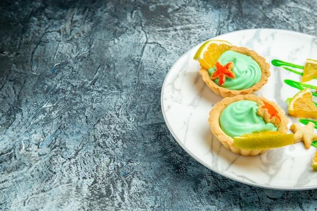 Вид снизу маленькие пирожные с кремом из зеленого теста и ломтиком лимона на тарелке на темной поверхности, свободное пространство