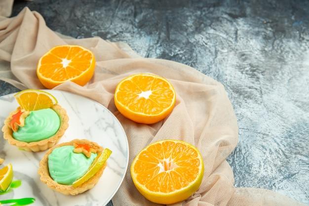 Vista dal basso piccole crostate con crema pasticcera verde e fetta di limone su piatto scialle beige tagliato arance su superficie scura con spazio libero