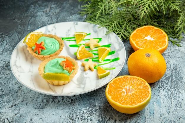 Vista dal basso piccole crostate con crema pasticcera verde e fetta di limone su arance tagliate a piatto su superficie scura