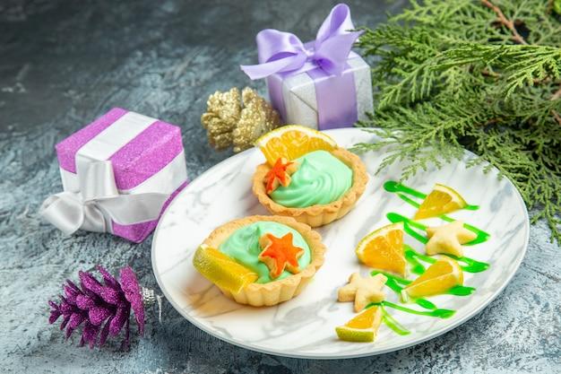 Vista dal basso piccole crostate con crema pasticcera verde e fetta di limone su piatto piccoli regali su superficie scura