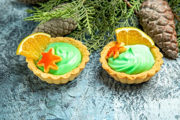 Piccole crostate vista dal basso con pigne di crema pasticcera verde su superficie grigia