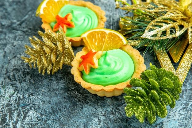 Piccole crostate vista dal basso con ornamenti natalizi con crema pasticcera verde su superficie grigia