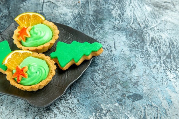 Вид снизу маленькие пирожные с зеленым кондитерским кремом, рождественское печенье на черной тарелке на серой поверхности с копией пространства