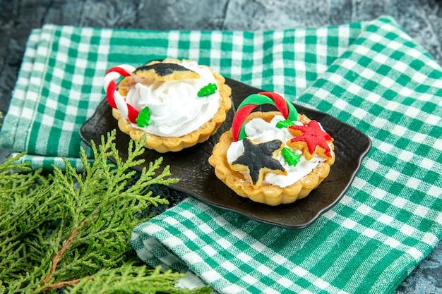 Маленькие рождественские пироги на черной тарелке на скатерти на сером столе, вид снизу