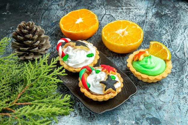 검은 접시 솔방울에 하단보기 작은 크리스마스 타르트 회색 테이블에 오렌지를 잘라