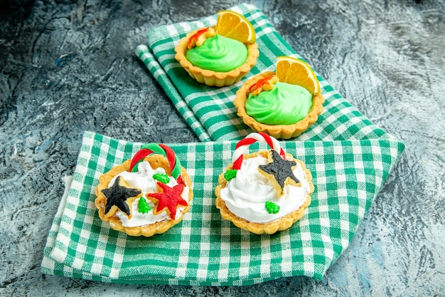 灰色のテーブルの上の緑の白い市松模様のテーブルクロスの底面図小さなクリスマスのタルト