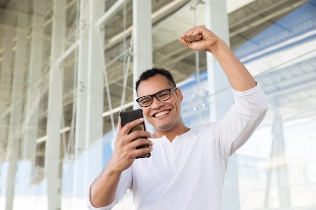 Bottom view of smiling young man finishing phone call, exulting