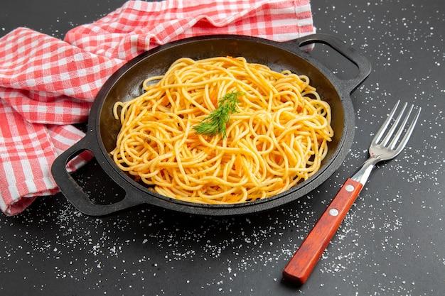 暗い背景に赤と白の市松模様のテーブルクロスの底面図スパゲッティフライパンフォーク
