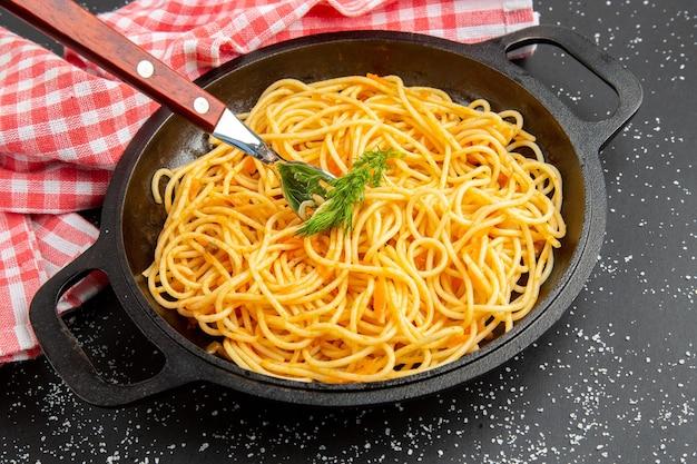 暗い背景に赤と白の市松模様のテーブルクロスの底面図スパゲッティフライパン
