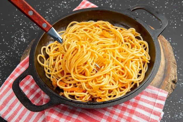 Bottom view spaghetti frying pan on wood board on dark background