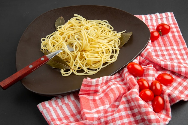Vista dal basso spaghetti con forchetta di foglie di alloro su piatto pomodorini da cucina a quadretti rossi e bianchi su tavola nera