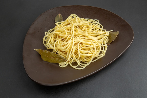 Bottom view spaghetti pasta with bay leaves on platter on black background