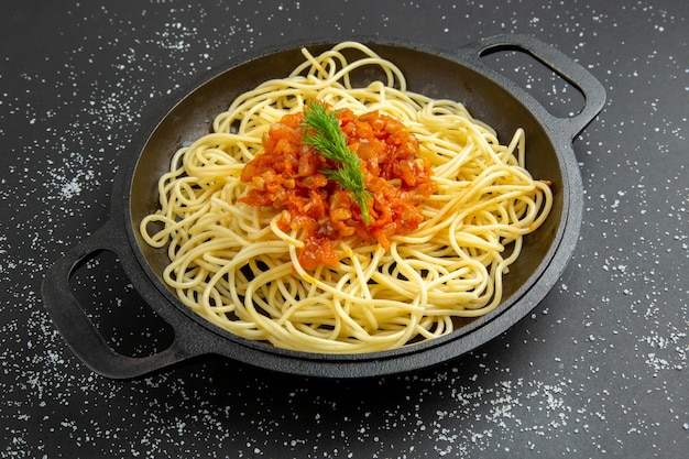 Bottom view spaghetti with sauce in frying pan on black table food photo