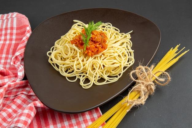 Spaghetti di vista dal basso con salsa sulla pasta cruda degli spaghetti del piatto sulla tavola nera