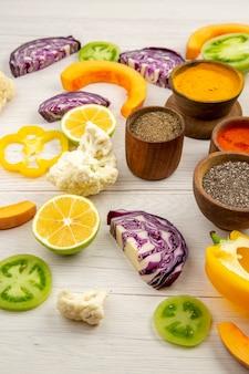 하단보기 향신료 그릇 콜리 플라워 잘라 피망 잘라 호박 잘라 붉은 양배추 흰색 테이블에 녹색 토마토를 잘라