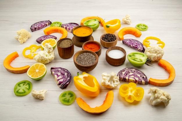 하단보기 향신료 그릇 잘라 피망 콜리 플라워 잘라 호박 잘라 붉은 양배추 잘라 테이블에 녹색 토마토
