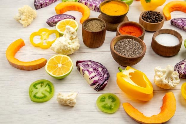 하단보기 향신료 그릇 잘라 피망 콜리 플라워 잘라 호박 잘라 붉은 양배추 흰색 테이블에 녹색 토마토를 잘라