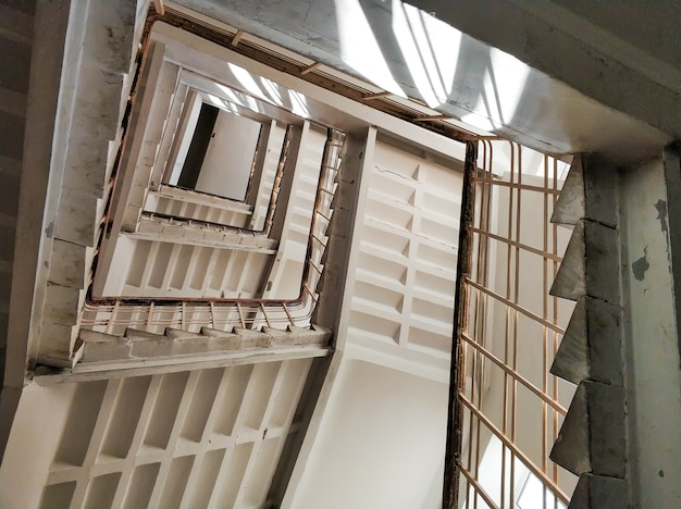 Bottom view of the stairwell of a tall building
