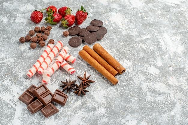 Vista dal basso fragole cioccolatini caramelle cereali cannella semi di anice sul lato sinistro del tavolo grigio-bianco con spazio libero