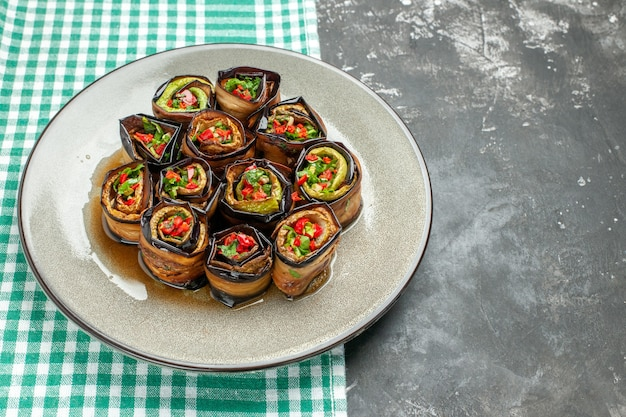 Vista dal basso involtini di melanzane ripieni in piatto ovale bianco tovaglia bianco-turchese su posto libero grigio