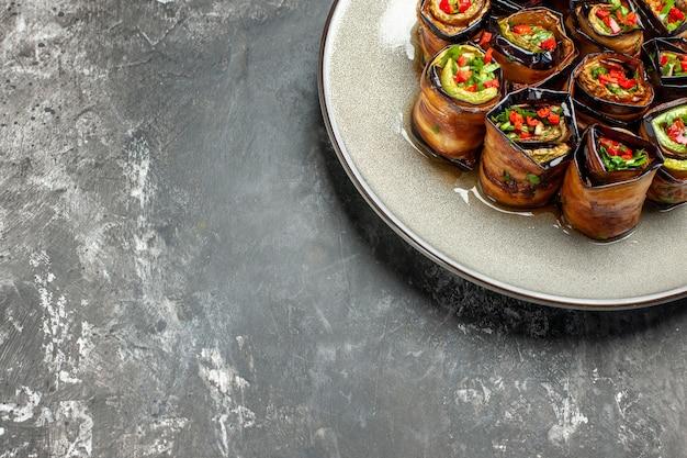 Involtini di melanzane ripieni vista dal basso su piatto bianco su sfondo grigio con spazio copia