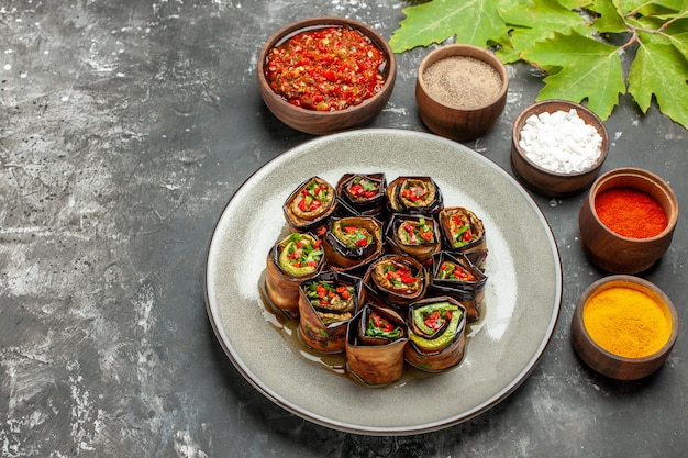 Bottom view stuffed eggplant rolls in white oval plate spices in small bowls salt pepper red pepper turmeric adjika on grey background free place