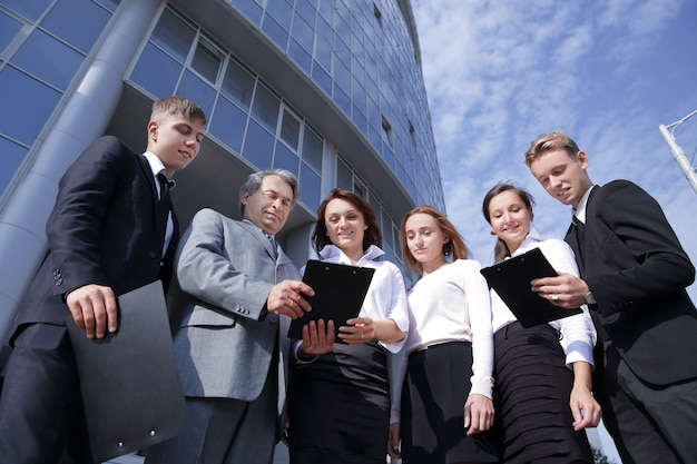 Bottom view.successful business people team standing together outdoors near modern office building