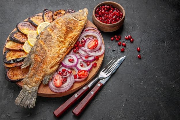 아래쪽 보기 맛있는 생선 튀김 튀긴 가지가 나무 판자에 양파를 자르고 어두운 배경에 다른 재료가 있습니다