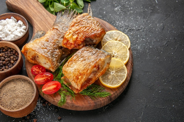 Vista dal basso gustosa frittura di pesce fette di limone tagliate pomodorini sul tagliere su sfondo nero