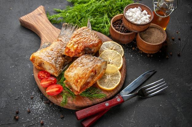 底面図おいしい魚のフライレモンスライスはまな板でチェリートマトをカットボウルナイフとフォークで黒の背景にさまざまなスパイス