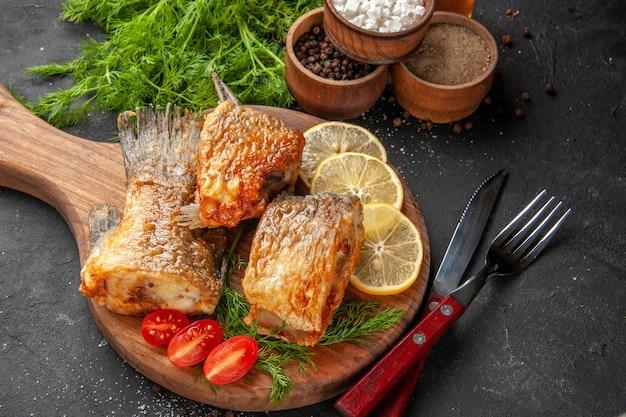 Вид снизу вкусная рыба, обжаренная, дольки лимона, нарезанные помидоры черри на разделочной доске, разные специи в мисках, нож и вилка на черном фоне