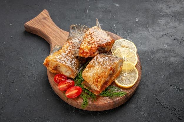 Вид снизу вкусная рыба, жареная, ломтики лимона, нарезанные помидоры черри на разделочной доске на черном столе