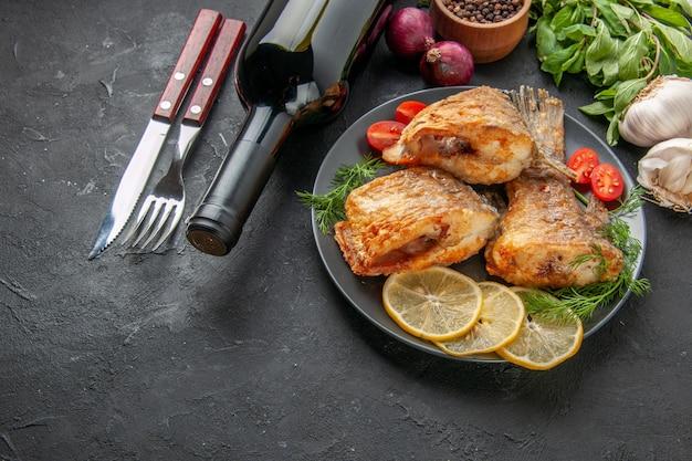 아래쪽 보기 맛있는 생선 튀김 레몬 조각은 접시에 체리 토마토를 자르고 검은 테이블에 딜 포크와 나이프 와인 병 마늘