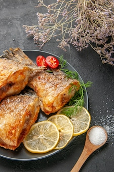 Вид снизу вкусная рыба, жареная, ломтики лимона, нарезанные помидоры черри на тарелке, ветка сушеных цветов на черном столе