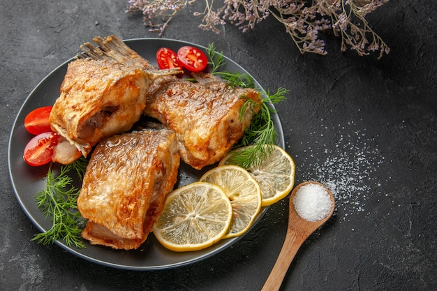 아래쪽 보기 맛있는 생선 튀김 레몬 조각은 접시에 체리 토마토를 잘라 검정 테이블에 말린 꽃 가지 나무 숟가락