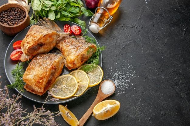 Vista dal basso gustosa frittura di pesce fette di limone tagliate pomodorini su piastra forchetta e coltello bottiglia di olio menta sul tavolo nero copia posto