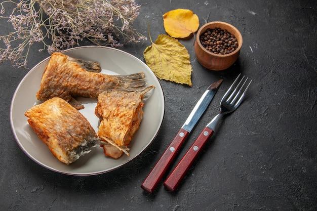 Вид снизу вкусная жареная рыба на тарелке, вилка и нож, ветка сушеного цветка, черный перец в деревянной миске на черном столе
