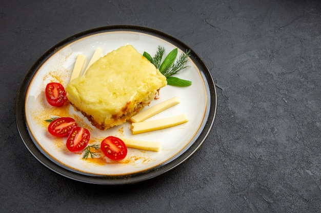 Vista dal basso gustose lasagne sul piatto su sfondo scuro copia posto