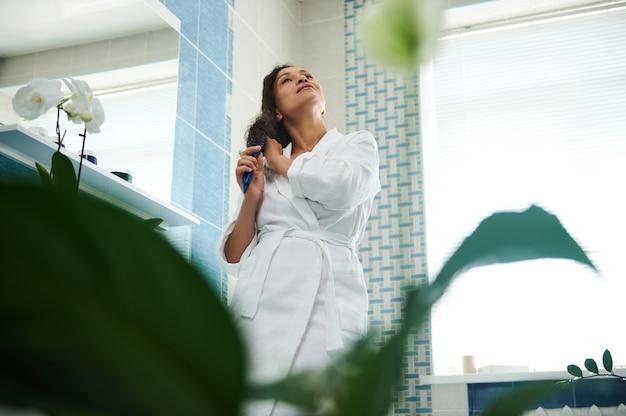 흰색 와플 목욕 가운을 입고 욕실에서 머리를 빗고 있는 젊은 혼혈 여성의 녹색 식물을 통한 밑면